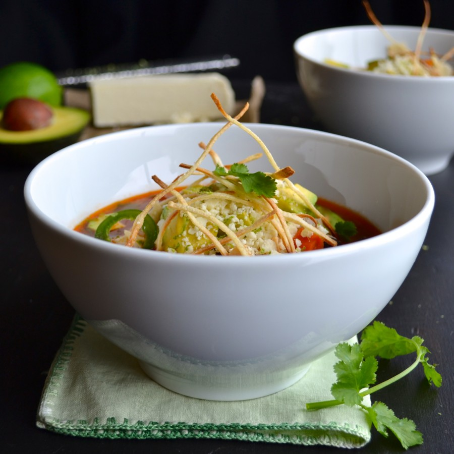 This is the most delicious Tortilla Soup recipe! Spicy, with complex flavors and topped with avocado, cotija cheese and thin crisp tortilla strips.   @tasteLUVnourish