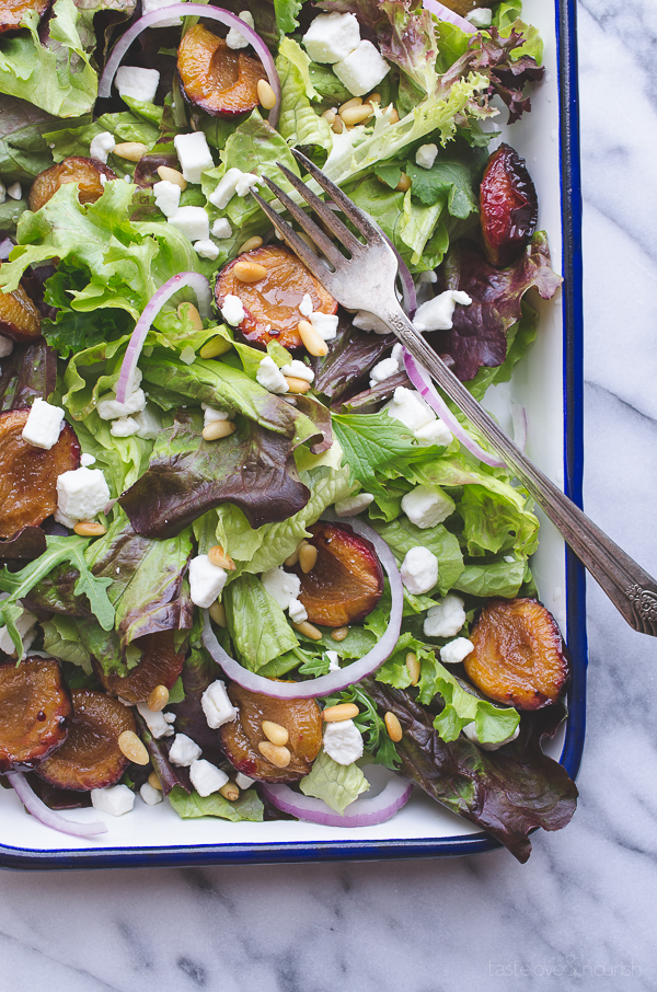 Mixed Greens with Roasted Italian Plums - these roasted plums add the most delicious flavor to this early fall salad topped with bits of creamy goat cheese and toasted buttery pine nuts. | @tasteLUVnourish on TasteLoveAndNourish.com