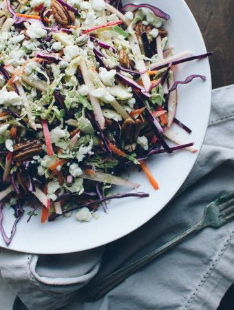 This crunchy Red Cabbage and Brussels Sprouts Slaw is my family's favorite salad! It's absolutely loaded with pecans, sunflower seeds, sweet apple slices and crumbles of blue cheese and topped with a Dijon Maple Vinaigrette. | @tasteLUVnourish