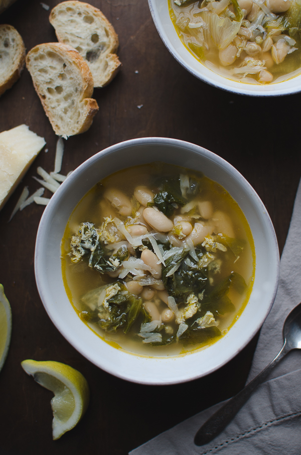 Escarole and Cannellini Bean Soup in Parmesan Broth - this recipe is amazing! Escarole and cannellini beans simmered in a light Parmesan broth then topped off with some lemon and more Parmesan. | @tasteLUVnourish