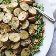 Lemon Dijon Potato Salad - this light potato salad is loaded with flavor from lemons, mustard, crunchy walnuts on a bed of baby arugula. This vegan recipe is a perfect potluck favorite! @tasteLUVnourish