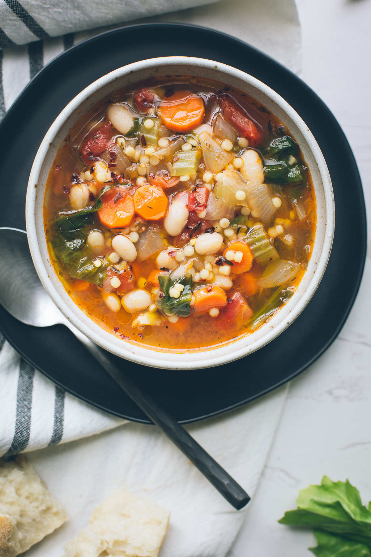This simple, warming Escarole White Bean and Tomato Soup, full of complex flavors, is so nourishing and easily adapts to whatever you've got on hand. Make this your go-to winter soup. Naturally vegan with gluten-free options. From @tasteLUVnourish