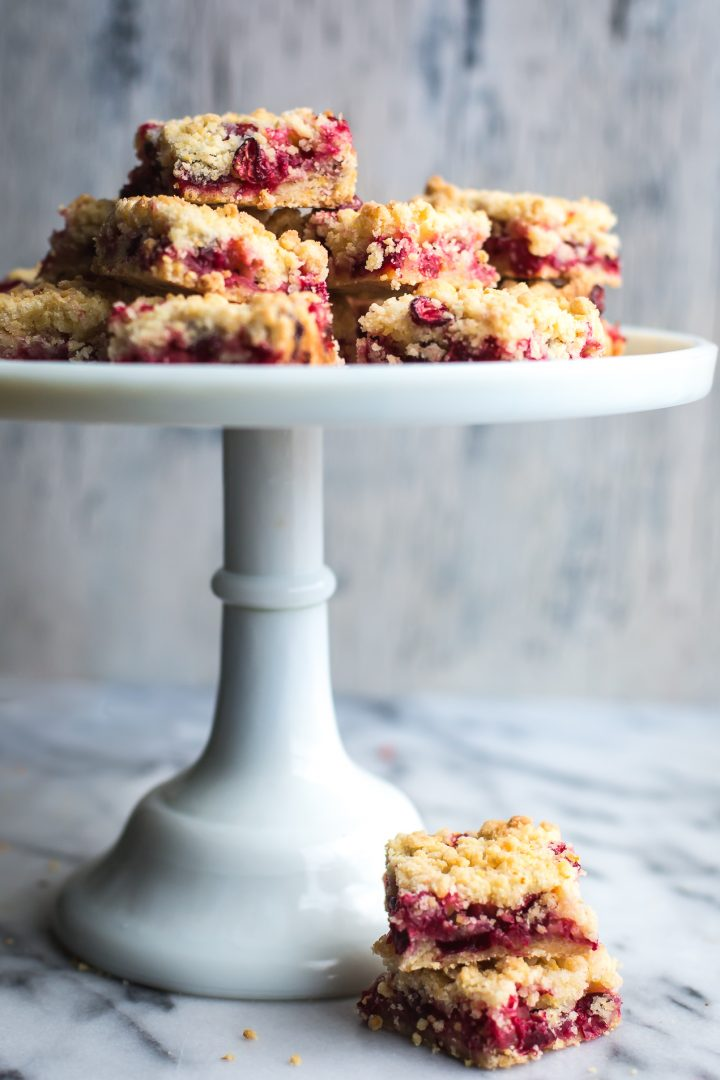 These Cranberry Bars are a simple, easy dessert that taste amazing! They've got a delicate, buttery, orange scented shortbread crust with a sweet, tangy cranberry filling. #tasteloveandnourish #cranberrybars #cookie #holiday #baking #recipe #easy #glutenfreeoptions